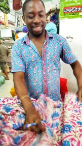 Shop assistant in dashing shirt and fluently and simultaneously conversing with his customers in Swaheli, English and Italian